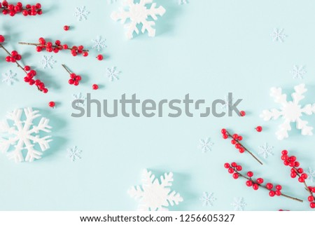 Christmas modern composition. Frame made of green fir tree branches, red berries and snowflakes on pastel blue background. Christmas, New Year, winter concept. Flat lay, top view, copy space #1256605327