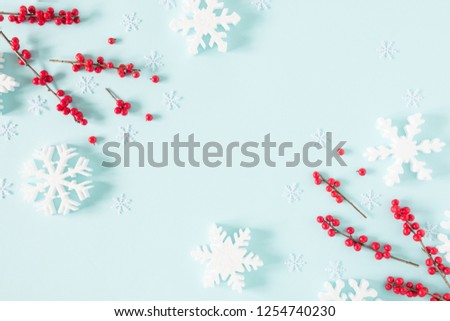 Christmas modern composition. Frame made of red berries and snowflakes on pastel blue background. Christmas, New Year, winter concept. Flat lay, top view, copy space #1254740230