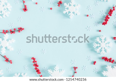 Christmas modern composition. Frame made of red berries and snowflakes on pastel blue background. Christmas, New Year, winter concept. Flat lay, top view, copy space #1254740236