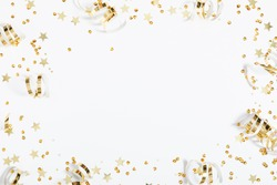 Christmas modern composition. Golden decorations, confetti, streamers, stars on white background. Christmas, New Year, winter concept. Flat lay, top view, copy space