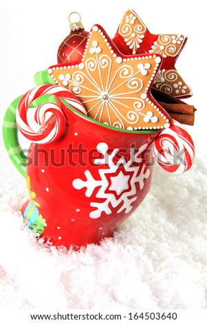 Christmas mug filled with gingerbread cookies and candy.