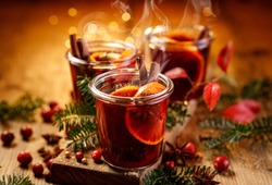Christmas mulled red wine with aromatic spices and citrus fruits on a wooden rustic table, close-up. Traditional hot drink at Christmas time