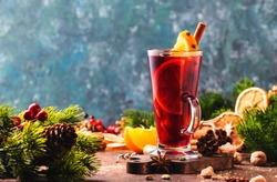 Christmas mulled red wine with spices and fruits in tall glass on wooden rustic table. Traditional Christmas or NewYear warming drink in festive table setting