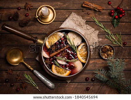 Christmas mulled red wine with the addition of spices and citrus fruits in a small vintage copper pan on a rustic wooden table, top view. Pot of mulled wine, traditional christmas drink. Stockfoto ©