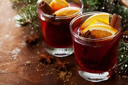 Christmas mulled wine or gluhwein with spices and orange slices on rustic table, traditional drink on winter holiday, magic light, selective focus