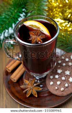 Christmas mulled wine with spices in glass and chocolate cookies, close-up, vertical