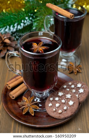 Christmas mulled wine with spices in glass and chocolate cookies, vertical