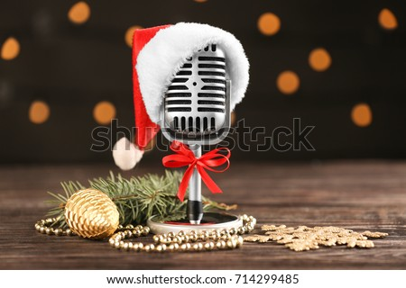Christmas music concept. Microphone with hat and decoration on wooden table #714299485