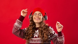 Christmas music. Pretty young woman in headphones and winter outfit dancing to her favorite song on red studio background, panorama. Lovely lady enjoying Xmas holiday playlist