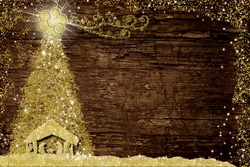 Christmas Nativity Scene and tree, religious greetings cards. Abstract freehand drawing of Nativity Scene and  Christmas tree with gold glitter on old wooden table with copy space.