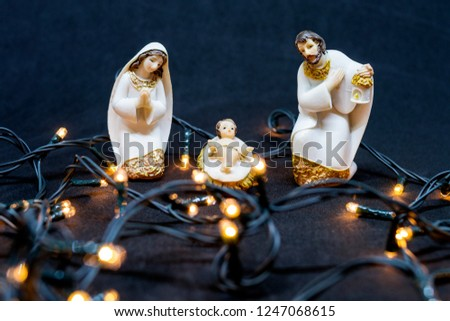 Christmas nativity with images of Mary, Joseph and Jesus, and decorative Christmas lights - black background