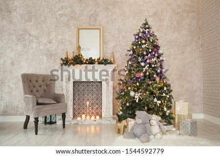 Christmas, New Year beige interior with beige texture wall background, brown armchair, white fireplace, mirror, decorated fir tree with garlands and balls, Christmas gifts, toys figures #1544592779