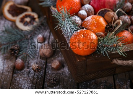 Christmas New Year  card. Tangerines,Nuts,Pomegranate,Citrus,Tree Branches  in a wooden box.Festive Background.Vintage style.selective focus.
