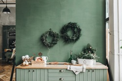 Christmas / New Year composition. Festive christmas decorations on the kitchen with handmade wreath made of fir branches, gold and white toys. Winter holidays concept.
