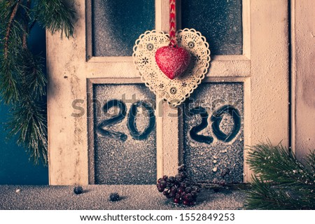 Christmas New Year decor - frame of snow-covered window with hand drawn 2020, fir branches, cones, and two decorative hearts. Cottage interior. #1552849253
