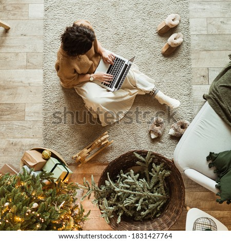 Christmas / New Year decorated home living room. Beautiful woman working on laptop. Decorated Christmas tree, wooden floor, pillows. Cozy comfortable interior design. Work at home. View from above.
