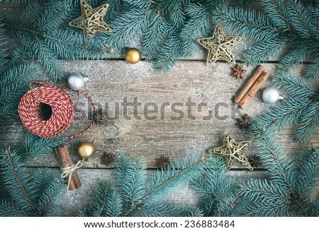 Christmas (New Year) decoration background: fur-tree branches, glass balls, golden glittering toy stars, decoration rope, cinnamon sticks and anise stars on a rough wooden desk with a copy space