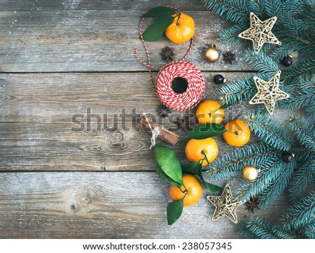Christmas (New Year) decoration background: fur-tree branches, glass balls, golden  toy stars, cinnamon sticks, anise stars and fresh mandarins on a rough wooden desk with a copy space. Top view