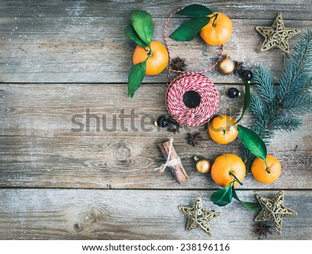 Christmas (New Year) decoration background set: fur-tree branches, glass balls, golden glittering toy stars and mandarines with green leaves on a rough wooden desk with a copy space. Top view