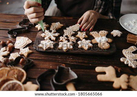 Christmas, New Year, DIY, holidays preparation and creativity concept. Getting ready to celebration. Woman hands decorating homemade gingerbread cookies with icing