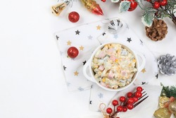 Christmas new year food, traditional festive olivier salad with fir branches and cones and decorations on a light table, idea for food design, place for recipe, flat lay, selective focus