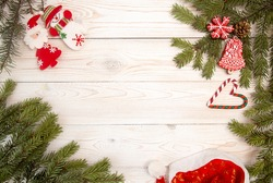 Christmas New Year holiday background. Gingerbread cookies, Santa Claus hat, snowman, Santa and fir branch tree on white table. Top view