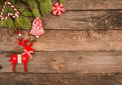 Christmas New Year holiday background. Greeting card with red gingerbread cookies, deer, candy cane and fir branch tree on old wooden table. Top view. Copy space