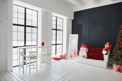 Christmas; New Year interior in black, white, red colours. Large window with table and chairs, wooden sofa on black wall background, fir tree with red balls