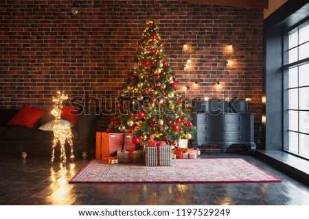 Christmas, New Year interior with red brick wall background, decorated fir tree with garlands and balls, dark drawer and deer figure #1197529249