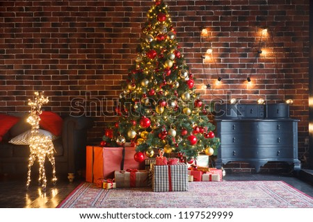 Christmas, New Year interior with red brick wall background, decorated fir tree with garlands and balls, dark drawer and deer figure