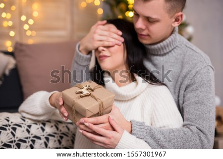christmas, new year, love and surprise concept - young man surprising his girlfriend with Christmas gift at home