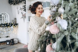 Christmas, New Year. Pretty and happy brunette in warm sweater decorating christmas tree at home