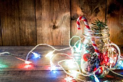Christmas, New Year's concept. Mason Jar with Christmas decorations, fir cones, artificial snow, candy cane and fir branch. On a wooden table background, with a lit garland turned on. Copy space