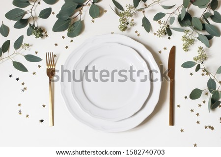 Christmas, New Year table place setting. Golden cutlery, porcelain plate, eucalyptus branches and golden confetti stars isolated on white background. Winter holidays background. Flat lay, top view. Сток-фото ©