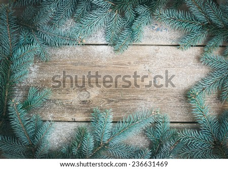 Christmas (New Year) theme background: a frame of fur-tree branches over a rough wooden desk with a copy space in the center