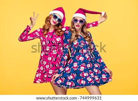 Christmas New Year. Two Young Girls in Santa hat Smiling. Having Fun Happy. Fashion. Pretty Sisters Friends. Woman in Trendy Red Holiday Dress. Colorful