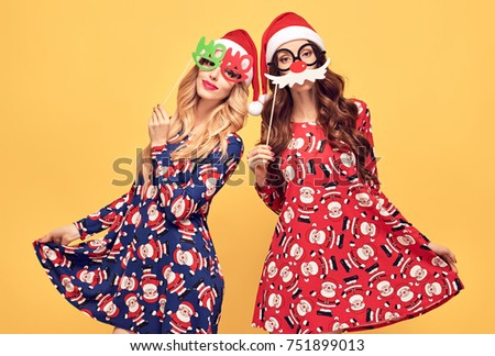 Christmas New Year. Two Young Woman with Props in Holiday Fashion Santa hat Having Fun Happy Smiling. Vintage. Playful Sisters Friends, Trendy Red Dress