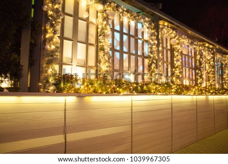 Christmas night. A beautifully enlightened building. The windows are decorated with fir branches. Large ones decorated with Christmas cherry trees.
