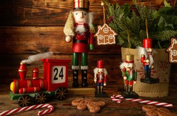 Christmas nutcracker figures, toy train Advent Calendar, gingerbread man cookies, candy canes and tree branches. Holiday season concept, composition on wooden background.