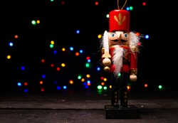 Christmas nutcracker wooden figure. Beautiful, festive toy soldier decoration, with colorful lights bokeh in background.