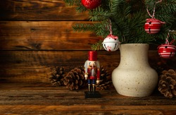 Christmas nutcracker wooden figure, cones and handmade ceramic flower vase with Christmas tree branches and decorative sleigh bells pendant ornaments. Beautiful, festive toy soldier with copyspace.