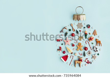 Christmas objects laid out in the shape of a Christmas bauble, overhead view #735964084
