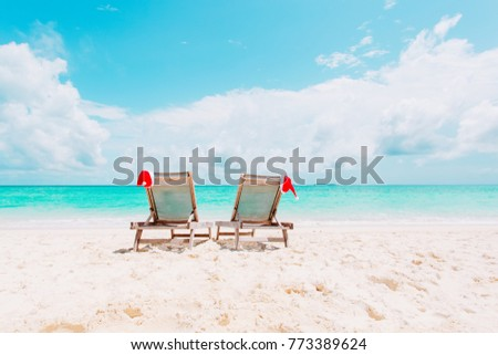 Christmas on beach -chair lounges with Santa hats at sea #773389624