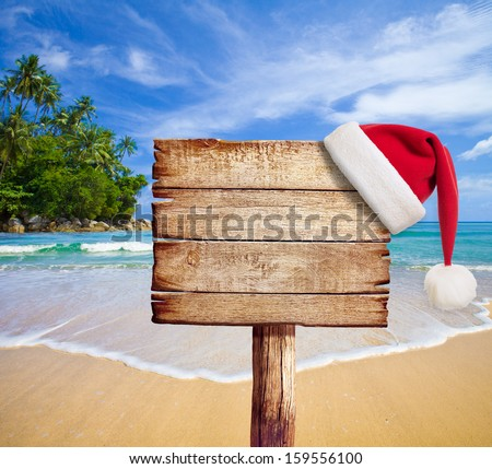 Christmas On Beach. Wooden Signboard With Santa\'S Hat.
