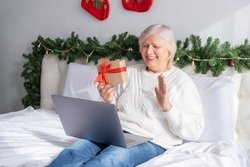 Christmas online greetings. happy senior women in Santa hat at home in bed with laptop.