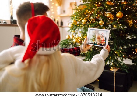Christmas online holiday. Young couple having  video call with their family or friends. Smiliтg couple in a santa hat  uses a digital tablet near decorated festive tree at home. Virtual meeting. Covid