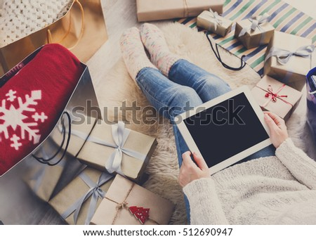 Christmas online shopping above view. Female buyer make internet order at screen of tablet. Woman buy presents prepare to xmas eve, among gift boxes and packages. Winter holidays sale