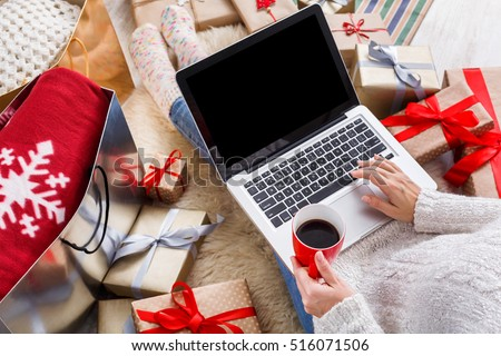 Christmas online shopping above view. Female buyer makes order on laptop, copy space on screen. Woman buy presents, prepare to xmas, among gift boxes and packages. Winter holidays sales