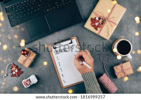 Christmas online shopping flat lay. Girl writing shopping list. Laptop, present box, cup of coffee, holiday decoration. Winter holidays sales