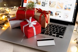 Christmas online shopping, sales and discounts promotions during the Christmas holidays, online shopping at home and lockdown coronavirus. Gifts and credit card on the laptop with blurred bokeh lights
